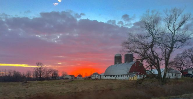red barn with colorful sunset behind it