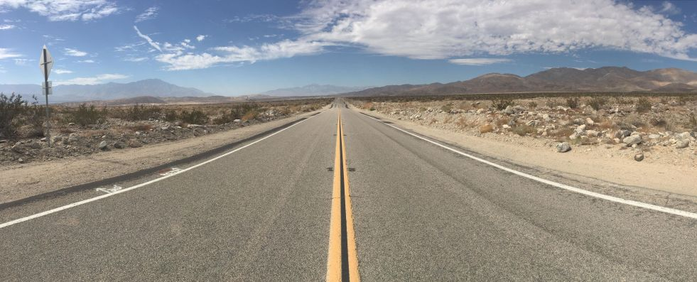 desert mountains road broad blue sky vanishing point