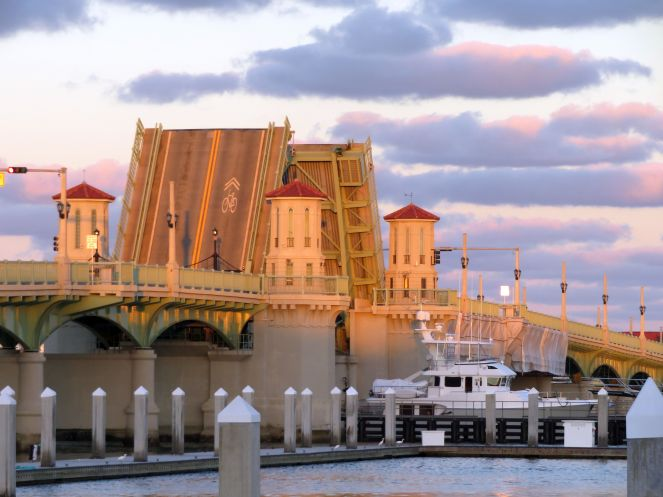 The sunset shines beautiful pink light on the drawbridge and clouds on A1A in St Augustine Florida