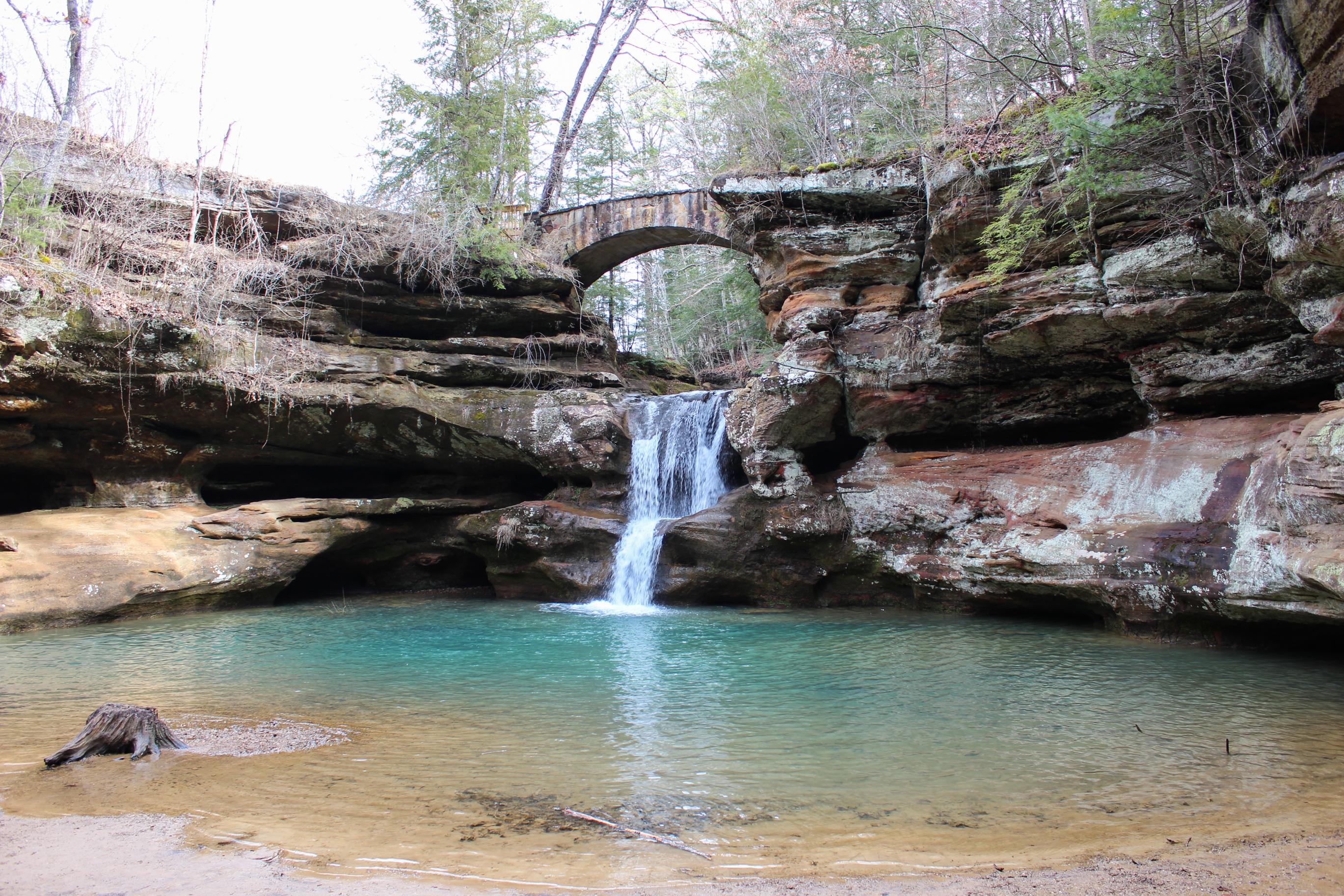 Upper falls under a stone arch bridge near old man's cave in hocking hills ohio
