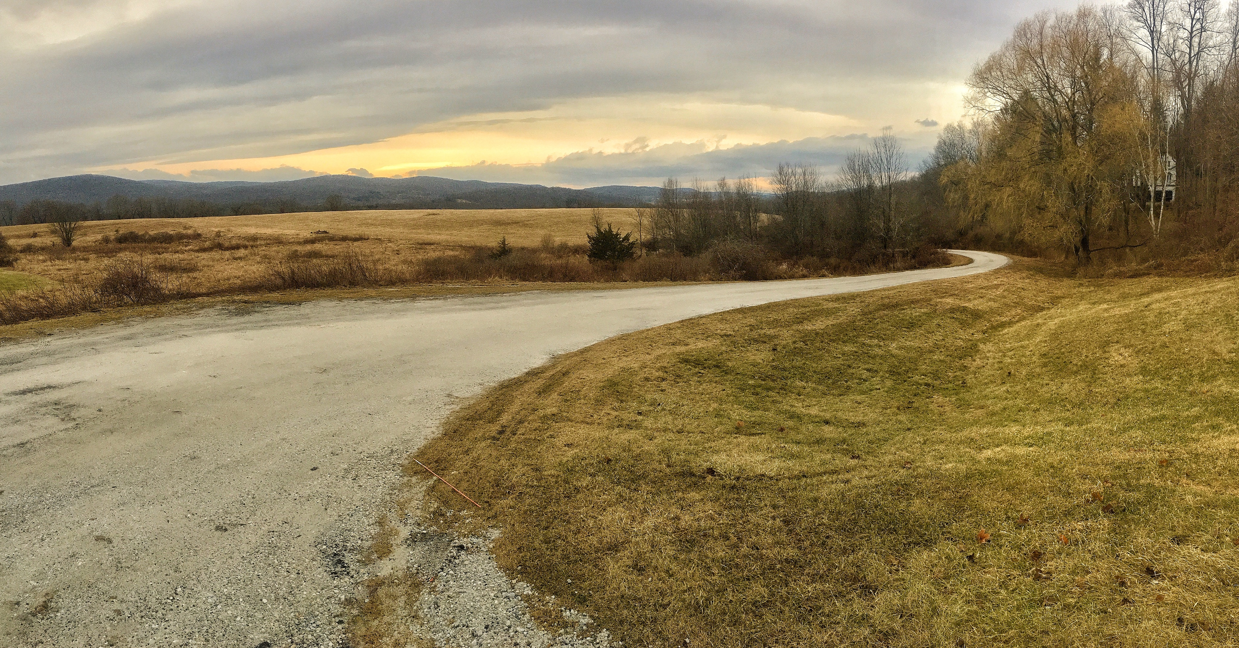 A gravel road meanders its way off in the sunset towards the foothills outside of Sherman CT