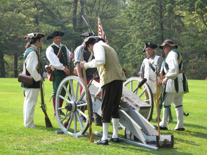 revolutionary war reenactment soldiers surround a cannon